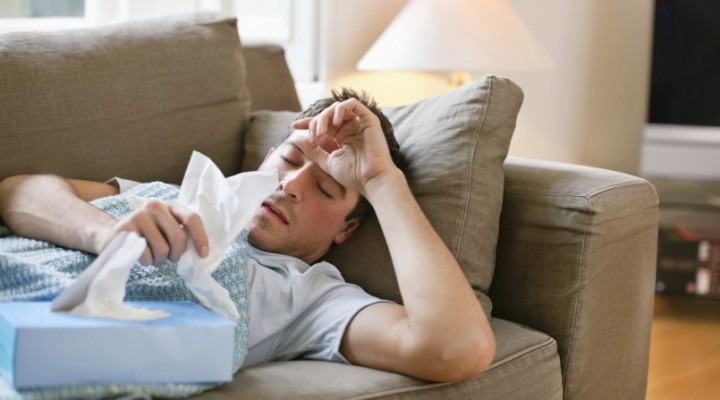 Sick man lying on couch
