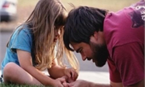 man checking little girl's toe
