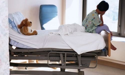 Child sitting on hospital bed