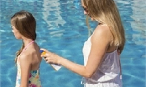 Mother spraying her daughter with sunscreen