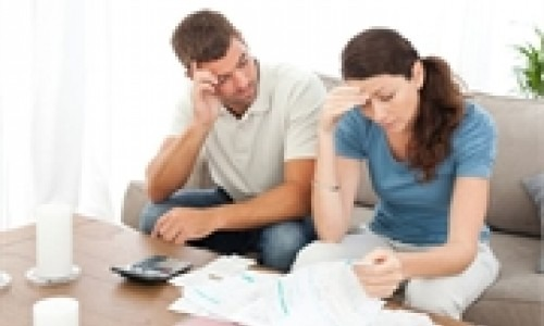 Two people looking though their financial bills