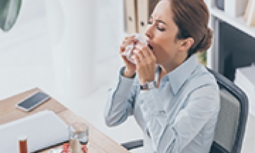adult businesswoman sneezing at workplace