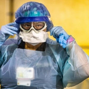TGH Team Member putting personal protective equipment on