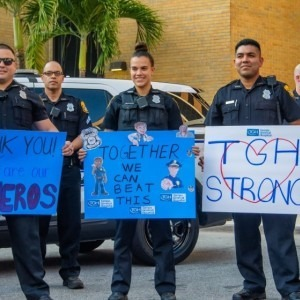 Tampa Bay Police officers show support with signs