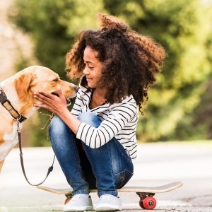 Young African American girl sitting on skateboard, petting Labrador retriever