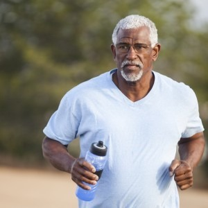African American male jogging outdoors with water bottle