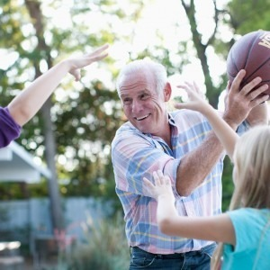Older gentleman playing basketball with two girls