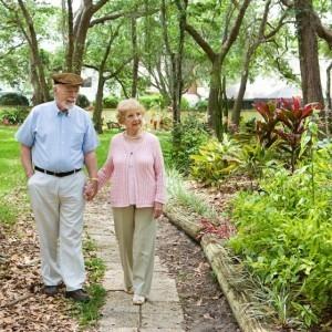 An elderly couple walking through a garden