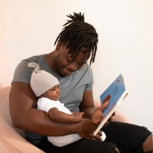 Man reading a book to his baby