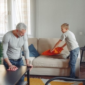 man and son cleaning the living room