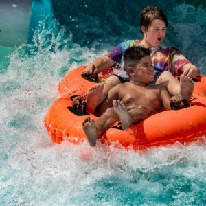 Two boys coming down a water slide