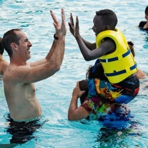 A man and boy give each other a high five in a pool