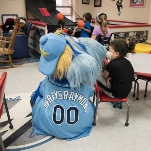 Tampa Bay Rays mascot Raymond sits with a patient in the Children's Medical Center at Tampa General Hospital.