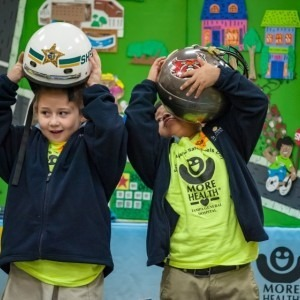 Two young boys trying on helmets