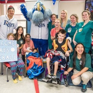 Rays Catcher Hank Conger poses for a group photo with children and staff at Tampa General Hospital.