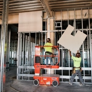 Workers hang drywall inside the TGH Brandon Healthplex.