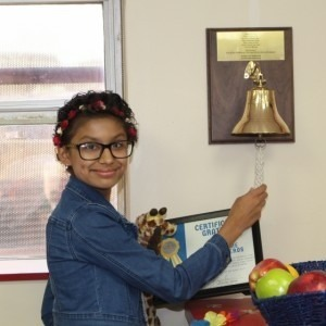 Teen girl ringing the chemo bell