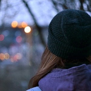 Image of a back of a woman's head looking at trees and lights