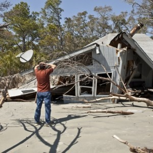 Man looking at the hurricane destruction of his house