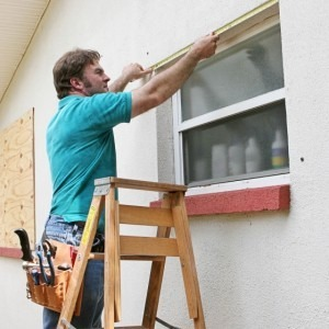 Man measuring a window to board up for Hurricane Irma