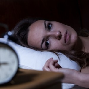 Woman laying in bed staring at the clock