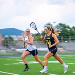 Two girls playing lacrosse