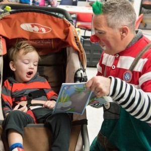 A ringling clown reading to a child in a stroller