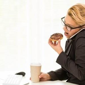 Woman eating a donut at work
