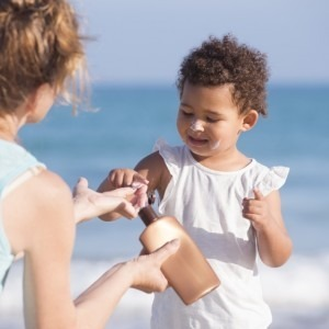 Woman applying sunscreen to a child
