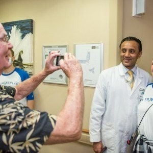 Man taking a photo of a female transplant patient and a male physician