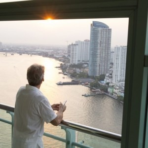 Man traveling overseas looking out a balcony