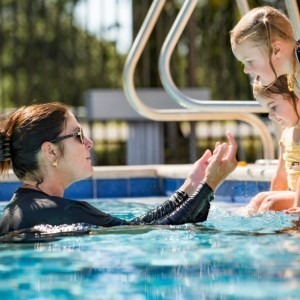 Woman teaching kids how to swim