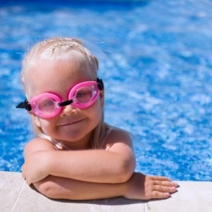 Young girl with goggles on in the swimming pool
