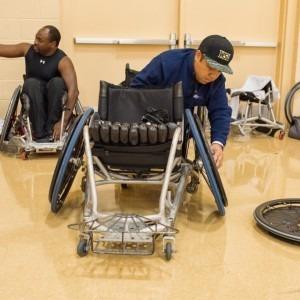 A man repairing a wheelchair at a wheelchair rugby event