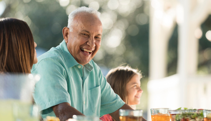 Elderly man laughing at dinner with his family