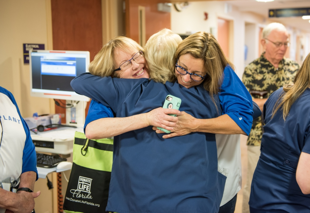 Female transplant patients hugging a female physician