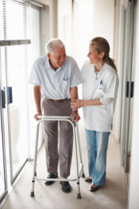 Nurse helps old man walk with walker