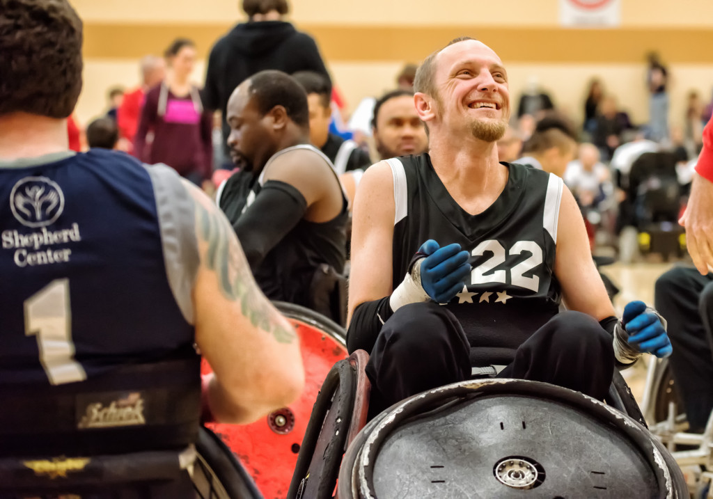 A smiling man particiapting in wheelchair rugby