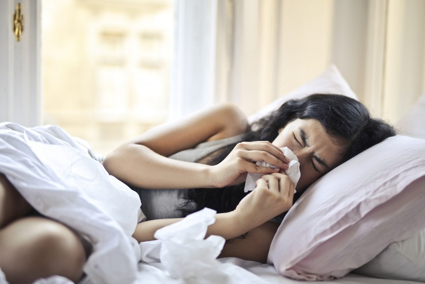 Woman lying in bed and blowing her nose
