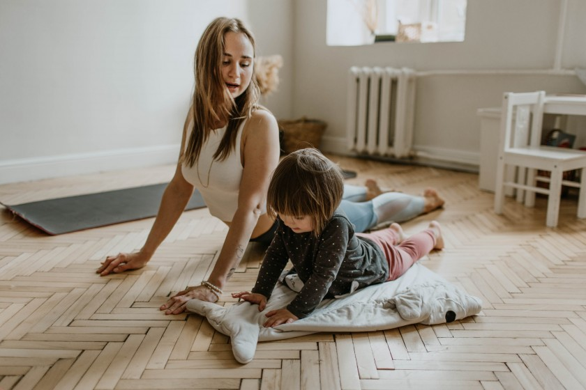 Woman doing yoga with her young child